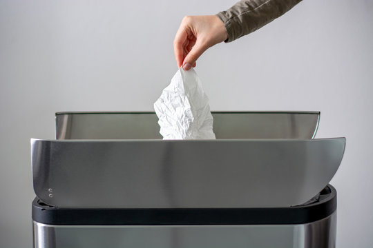 Women hand throwing a white used crumpled tissue paper into a garbage trash bin. Coronavirus advice includes use a disposable paper tissue.