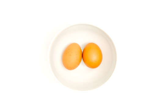 Two brown eggs isolated In a white cup on white background