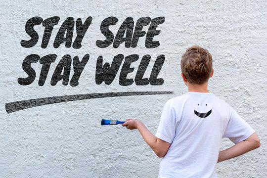 Männliches Kind vor einer weißen Wand mit dem Text STAY SAFE STAY WELL