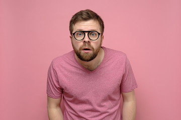 Man with glasses is confused, he leaned forward, looks with a shocked expression on his face and does not believe what he saw.