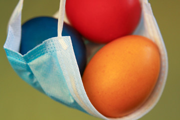 Vivid colored eggs in medical mask Easter 2020