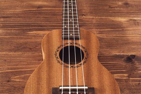 beatiful soprano ukulele with white strings made of zebrawood on aged wood background
