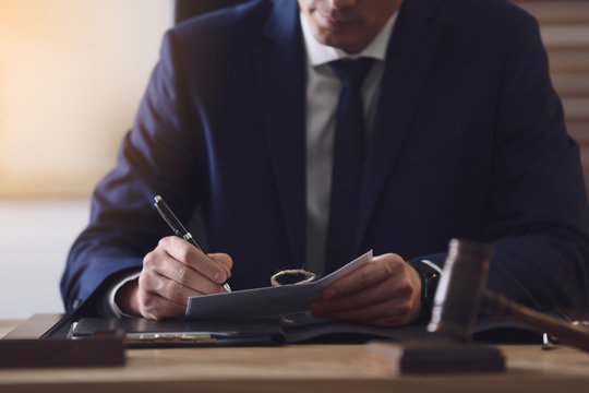 Male lawyer working at table in office, closeup