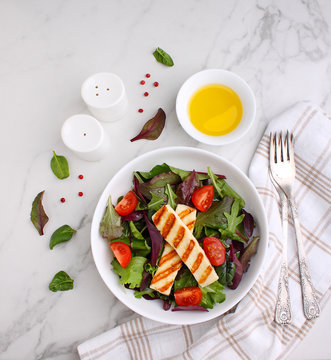 Green salad with fried halloumi cheese in a white plate on a marble background, top view.