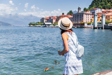 Wall Mural - Lake Como, town Bellagio, Italy. Lovely girl tourist feeding the ducks during vacations on lake Como in Italy. Italian vacations background.