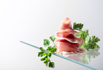 Fototapete - Prosciutto with parsley on a glass table.