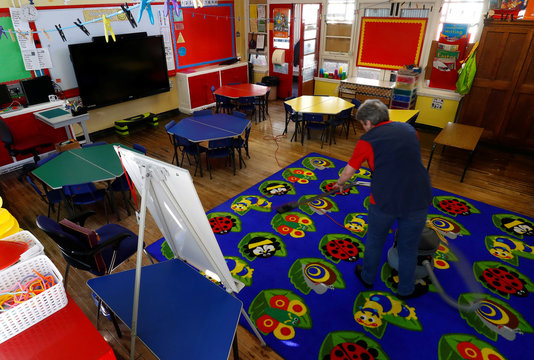 A member of staff cleans a empty classroom at Nettlefield Primary School as the majority of schools in the UK close while the spread of the coronavirus disease (COVID-19) continues