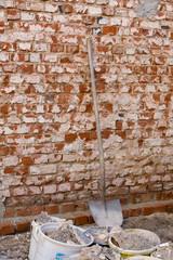 Eine Schaufel an einer alten Ziegelmauer.