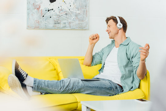 Side view of smiling man in headphones singing while sitting with laptop on sofa