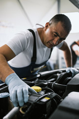 Car service mechanic worker standing in front of car engine open hood and working