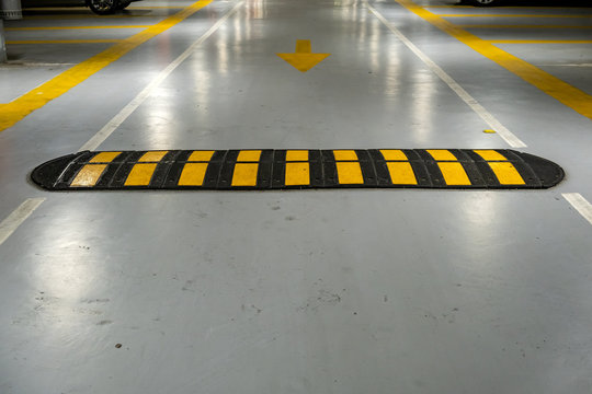 Striped black and yellow speed bump on a road.