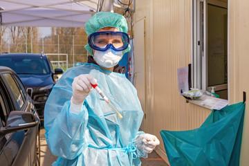 Ärztin an einer Teststation mit Coronavirus Test in der Hand