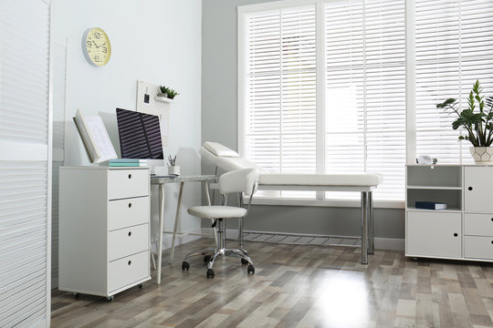 Modern medical office interior with computer and examination table