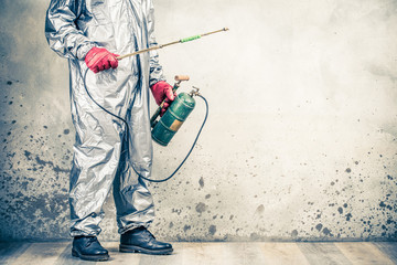 Pest control worker in protective uniform spraying pesticide with old vintage disinfectant sprayer. Preventing the spread of disease respiratory syncytial virus coronavirus COVID-19. Retro style photo