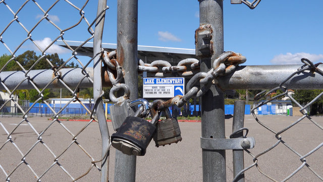 Close up of locked gate on a school closed due to coronavirus. All logos removed.
