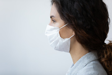 Profile close up view face of young serious woman wearing protective medical mask on blue...