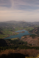 Urkulu reservoir surronded by mountains seen from the top of Orkatzategi hill, in Aretxabaleta, Basque Country.