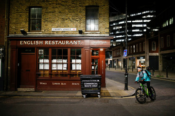 A food delivery man cycles past a closed restaurant, on the day Prime Minister Boris Johnson ordered all restaurants to close in response to the number of the coronavirus disease (COVID-19) cases continuing to grow, in London