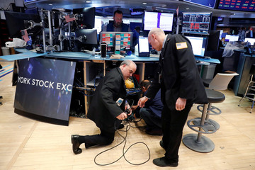 Traders remove computer equipment to work from home on the floor of the New York Stock Exchange (NYSE) as the building prepares to close indefinitely due to the coronavirus disease (COVID-19) outbreak in New York