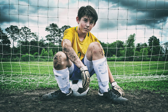 Male child soccer player sitting in the muddy goal