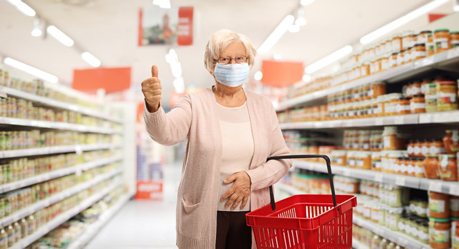 Elderly woman shopping in a supermarket with a protective face mask showing thumbs up