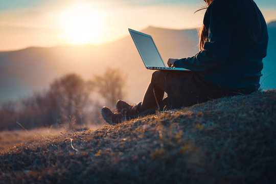 Using laptop computer in nature, technology and freedom concept