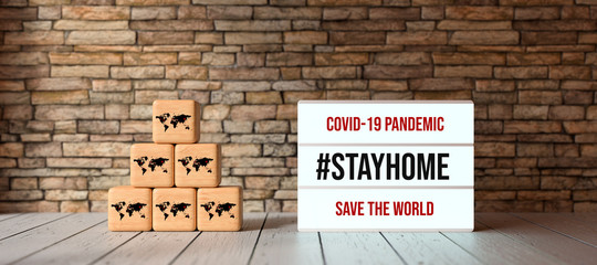 Fotorolgordijn Londen lightbox with message COVID-19 PANDEMIC #STAYHOME and cubes with world map symbols in front of brick wall on wooden floor