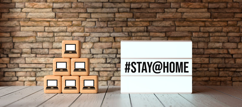lightbox with message #STAY@HOME and cubes with computer symbols in front of brick wall on wooden floor