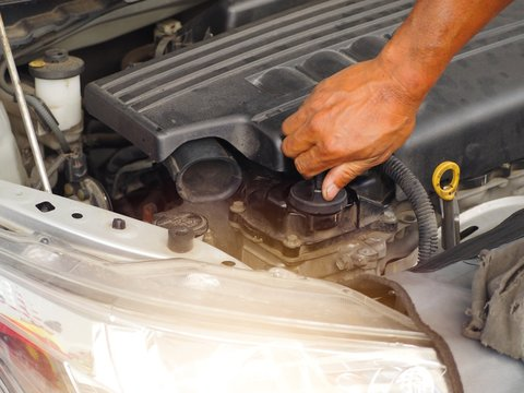 Hand is twisting the engine oil cap.Car maintenance technician He is checking the auto engine, car inspection center.