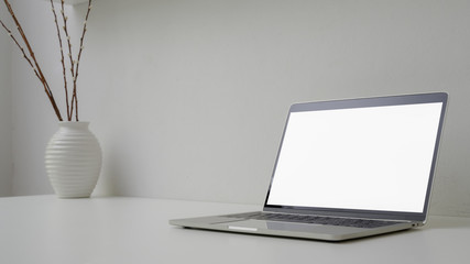 Cropped shot of minimal workspace with open blank screen laptop, vase and copy space