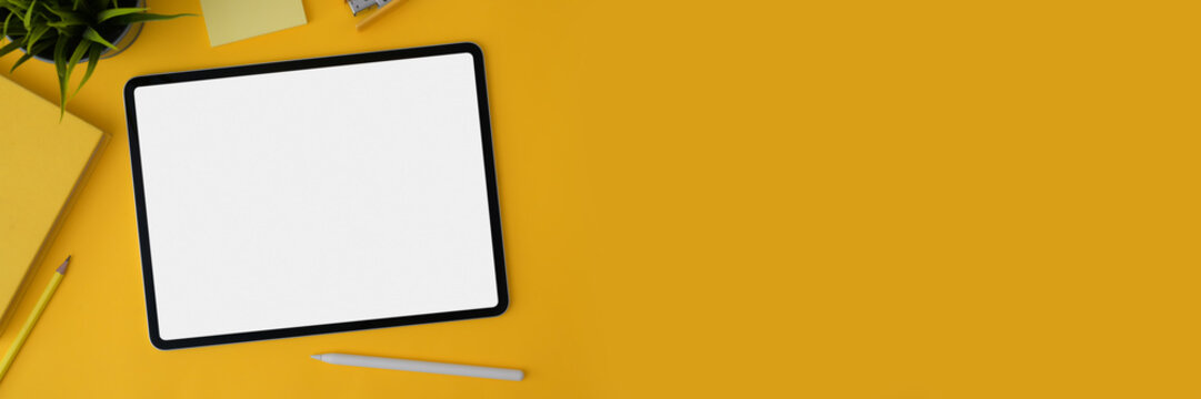 Cropped shot of blank screen tablet with stylus and stationery on yellow background