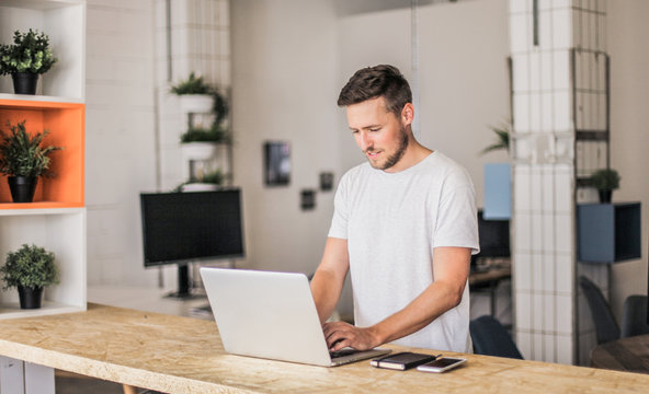 happy smiling remote online working man typing and with laptop, mobile phone and notebook in white shirt standing up in front of a work desk in an coworking office