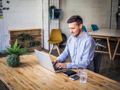 concentrating and  typing remote online working man in casual outfit with laptop, mobile, glass and and notebook sitting in an coworking office at a work desk