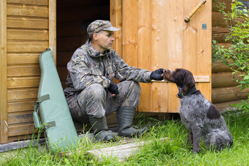a hunter sits in the doorway of a wooden house and caresses a dog