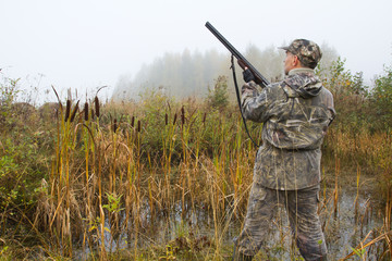 the hunter stopped at the edge of the swamp with his shotgun ready