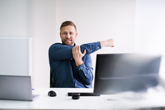 Close-up Of Businessman Stretching His Hands At Workplace