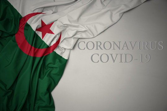 waving national flag of algeria on a gray background with text coronavirus covid-19 . concept.