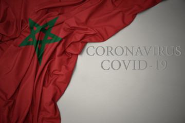 Poster Maroc waving national flag of morocco on a gray background with text coronavirus covid-19 . concept.