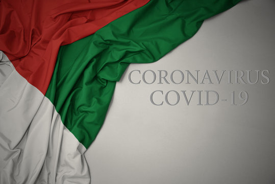 waving national flag of madagascar on a gray background with text coronavirus covid-19 . concept.