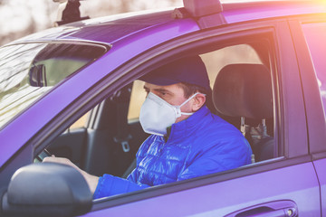 A man in medical face mask (respirator) during an epidemic in the car