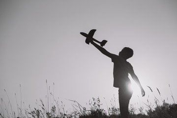 Black silhouette of young caucasian kid isolated on sunny sunset sky background. Boy playing toy plane outside on grassy summer hill. Setting big goals and dreaming about happy future concept.