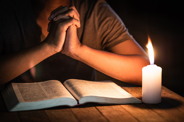 Religious concepts, The young man prayed on the Bible in the room and lit the candles to illuminate.