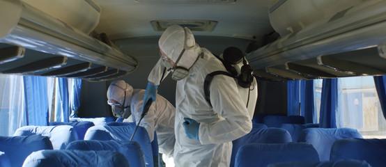 HazMat team in protective suits decontaminating public transport tourist bus interior during virus outbreak Fototapete