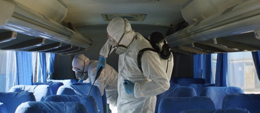 HazMat team in protective suits decontaminating public transport tourist bus interior during virus outbreak