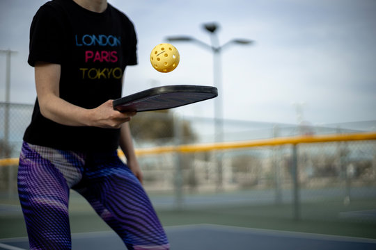 Woman playing pickleball match with whiffle ball and pickle ball paddle