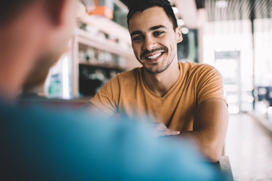 Cheerful young male friends having meeting in cafe