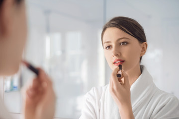 A young woman putting on lipstick