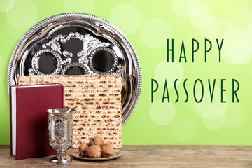 Symbolic Pesach (Passover Seder) items on wooden table against green background Wall mural