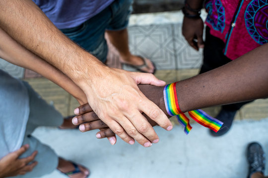 Detail of a group of hands from different ethnic groups with an lgtb flag