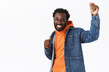 Cheerful, carefree and relaxed handsome stylish african-american guy having fun, dancing and partying enjoy spooky halloween holiday, raising hands up delighted, smiling, stand white background
